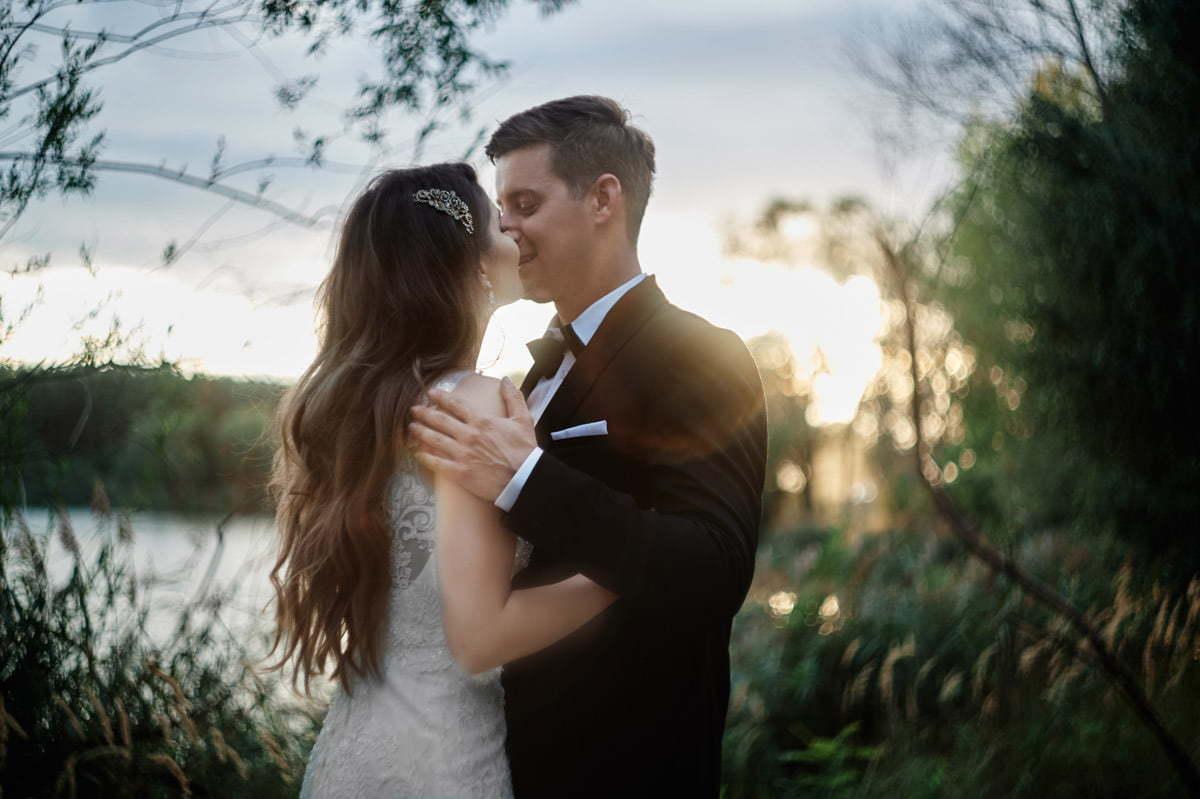 Para młoda całująca się w tle jeziora
