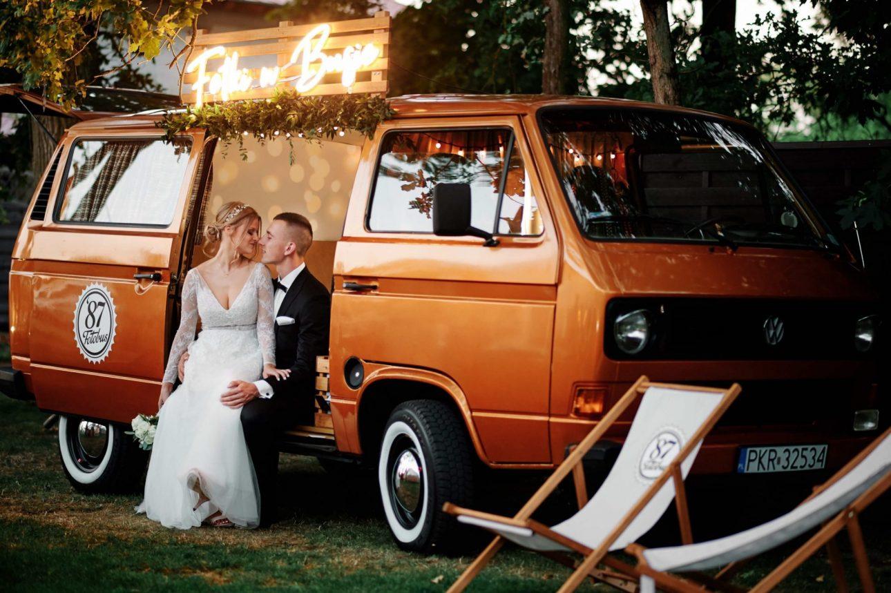 fotografia ślubna przedstawiająca parę młodą w starym stylowym samochodzie
